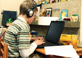 Student with headphones working on a computer
