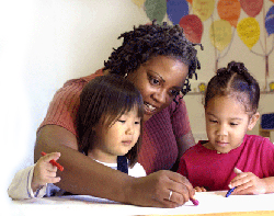Photo of an afterschool staff member coloring with two young girls.