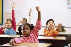 Photo of children at desks in a classroom with hands raised