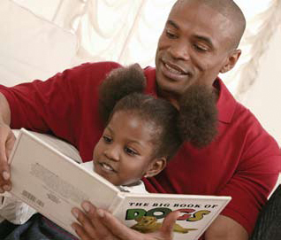 Photo of a father reading to a child.