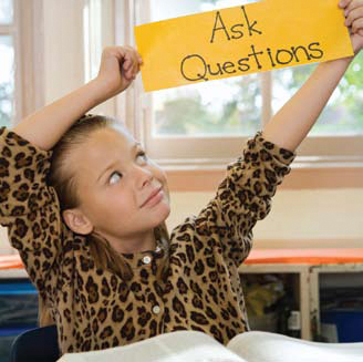 Photo of a student holding a sign with the words 'Ask Questions'.