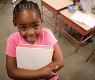 Photo of a girl smiling with a book in her hands.