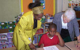 Photo of two teachers helping a student.