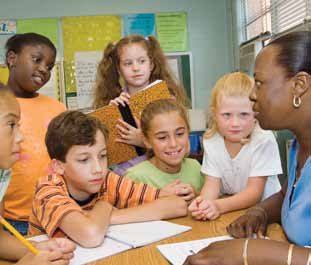 Photo of a teacher at her desk talking with several students.