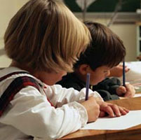 Photo of two children writing at a desk.