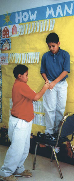 Photo of two boys putting up a banner at a school.