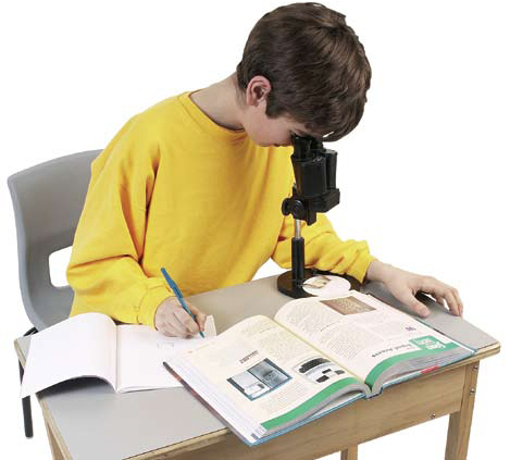 Photograph of a boy looking in a microscope.