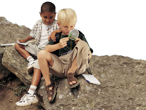 Photo of two children sitting outside on a rock viewing an object under a magnifying glass.