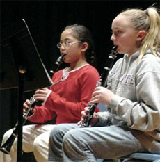 Photo of two girls playing musical instuments.