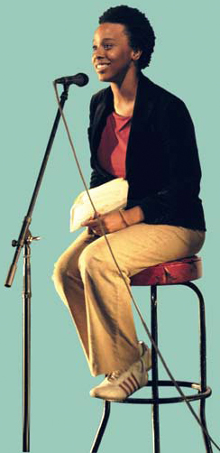 Photo of a woman sitting on a stoll talking into a microphone.