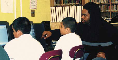 Photo of a teacher pointing out something on a computer to two students.