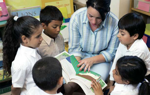 Photo of a teacher reading to several young students