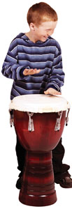 A photo of a boy playing the drums and learning about rhythm.