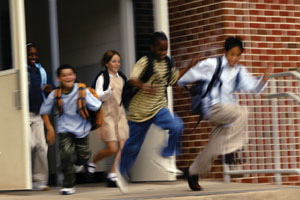Photo of children running out the school door after the bell rings.
