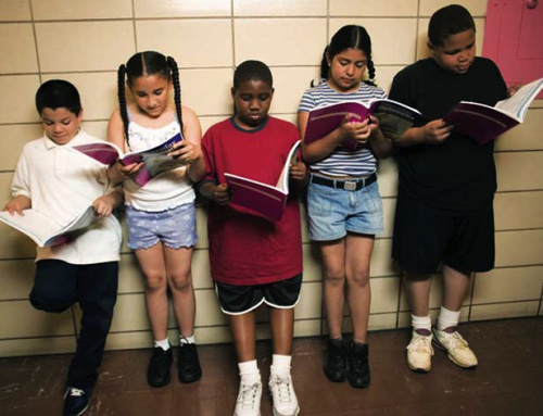 photo of five children standing and reading in a hallway