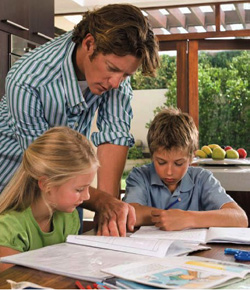 Photo of a father reviewing homework with his two children.