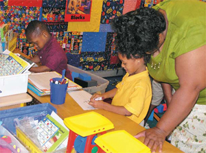 Preschoolers work in a writing center