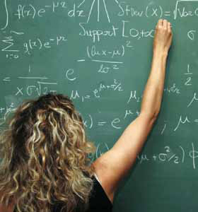 Photo of a girl writing a math equasion on the chalkboard.