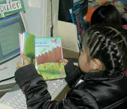 Photo of a girl at a computer reading a science lesson.