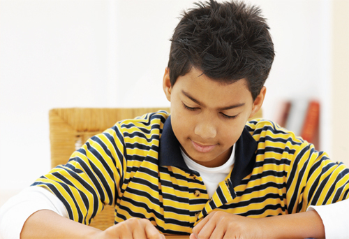 Photo of a boy reading at a desk.