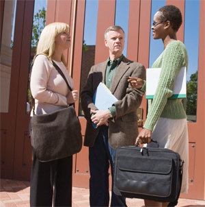 Photo of two women and a man dressed in business attire talking outside a building.