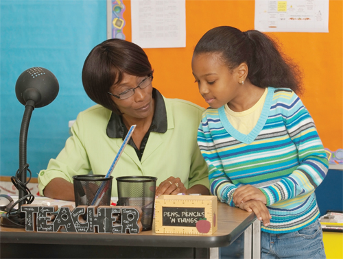 Photo of a teacher and student at the teachers desk, reading a book.