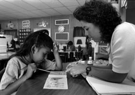 Photo of teacher and student working at a school desk.