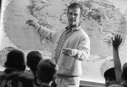 Photo of a teaching showing a world map to a group of students.