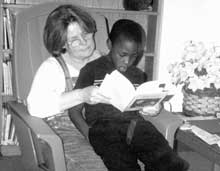 Rapoport Academy director Nancy Grayson takes time out to read with one of her students.